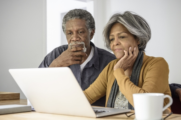 Photo of married couple reading information on a computer