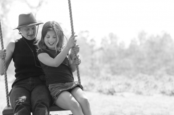 cancer survivor and daughter on a wooden swing