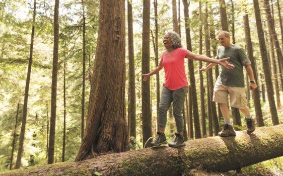 Man and woman balancing on a log