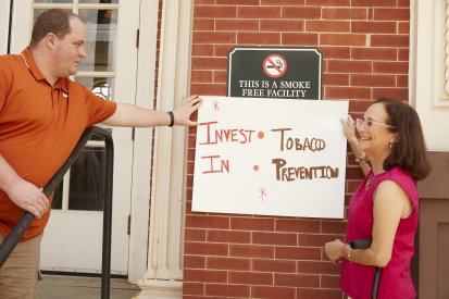 volunteers hold up anti-smoking sign