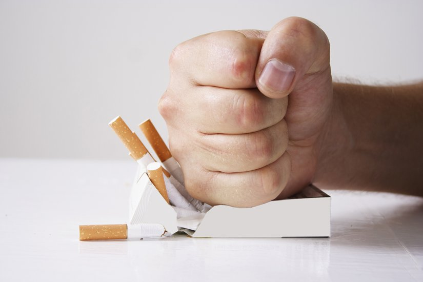 Photo of a hand crushing a pack of cigarettes