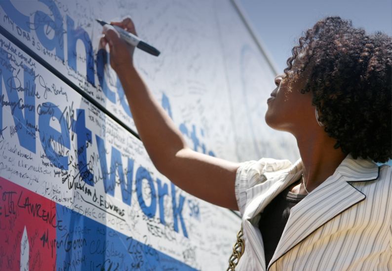 Photo of ACS CAN supporter signing the Fight Back Express bus at an event